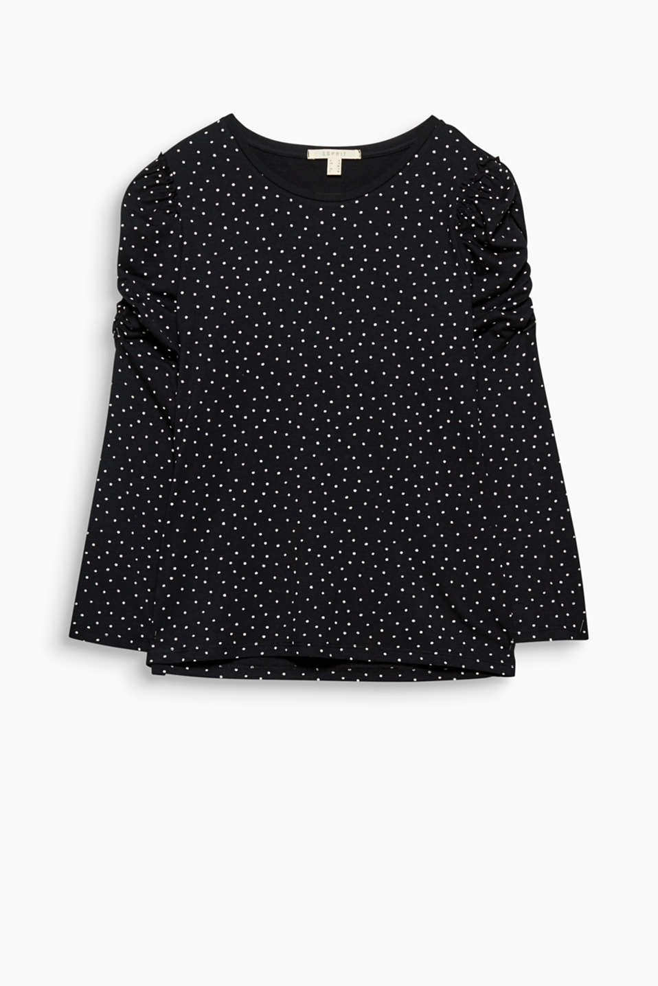 Polka dots, feminine gathers and frills give this soft top its charming look