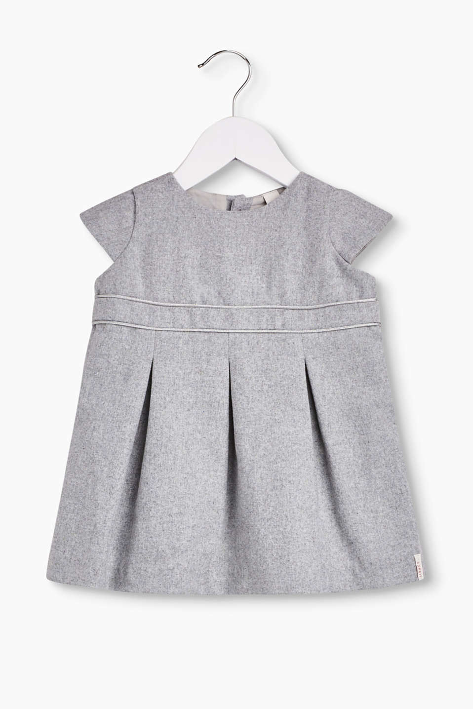 This grey flannel dress stands out with its swirling width and waist panel with shimmering piping