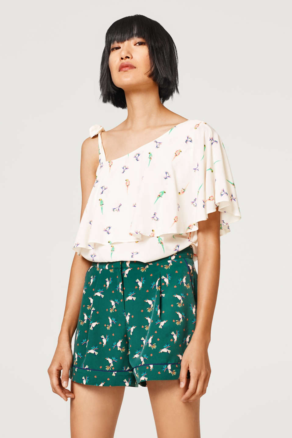 Asymmetric blouse top with a parrot print