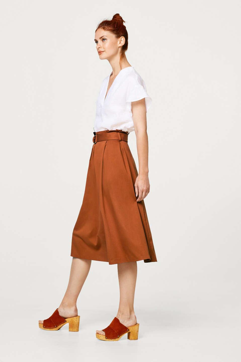 Denna svepande kjol har feminin charm tack vare trendig midilängd och modern paperbaglinning med lagda veck och skärp!