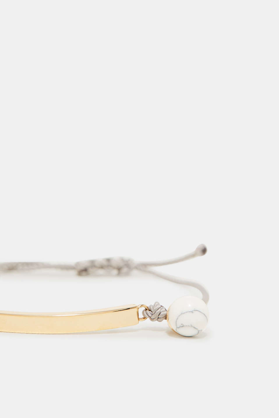 Fine cord bracelet with a silver charm