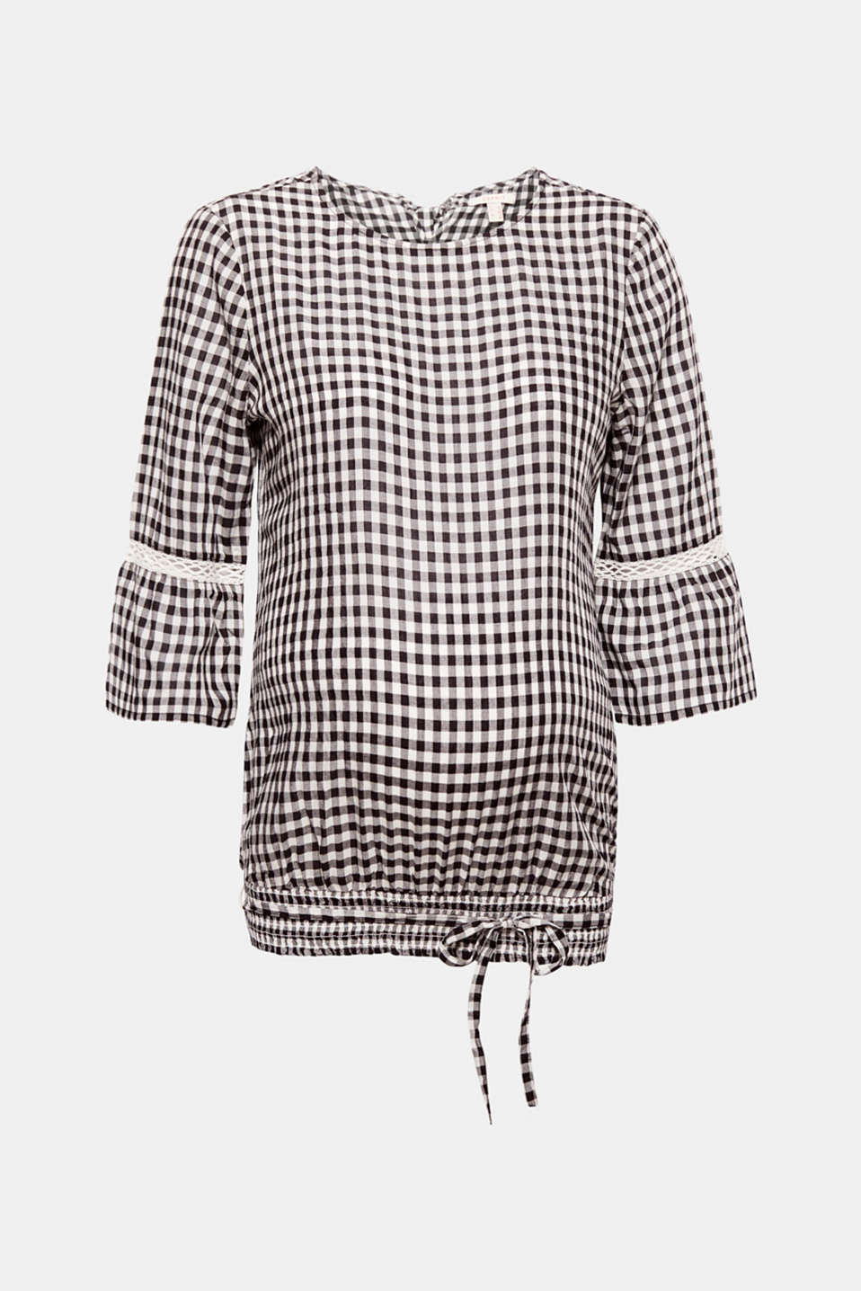 This flowing blouse gets its charming look from the classic gingham check pattern, the three-quarter length sleeves with lace details and the bow at the back of the wide, round neckline.